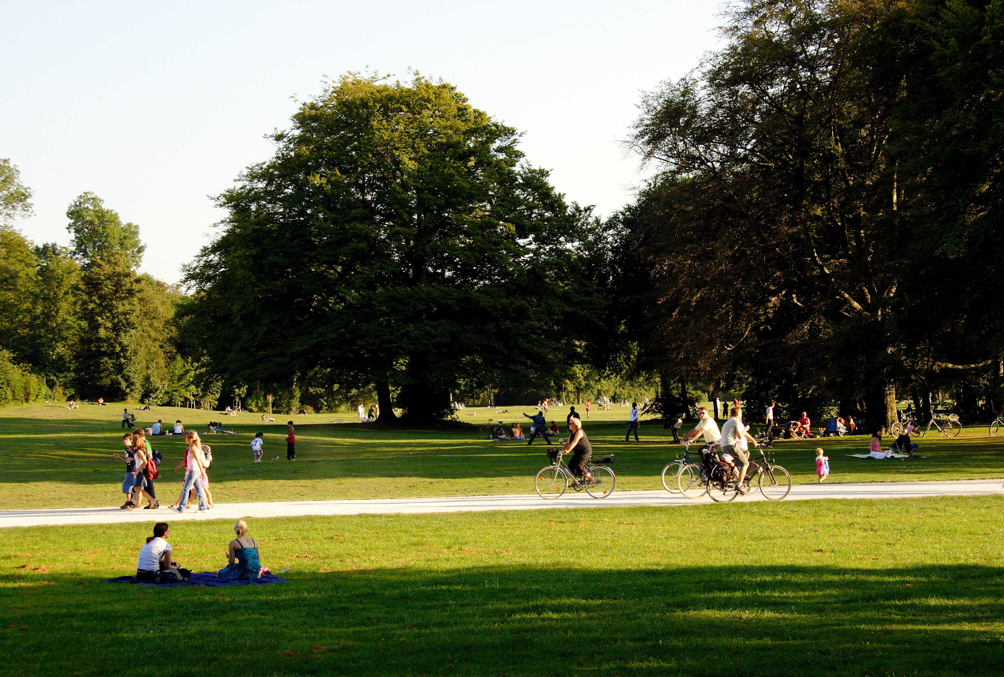 Many people enjoy the afternoon sun on the meadows of the English Garden, sitting and lying; others walk or ride a bicycle.