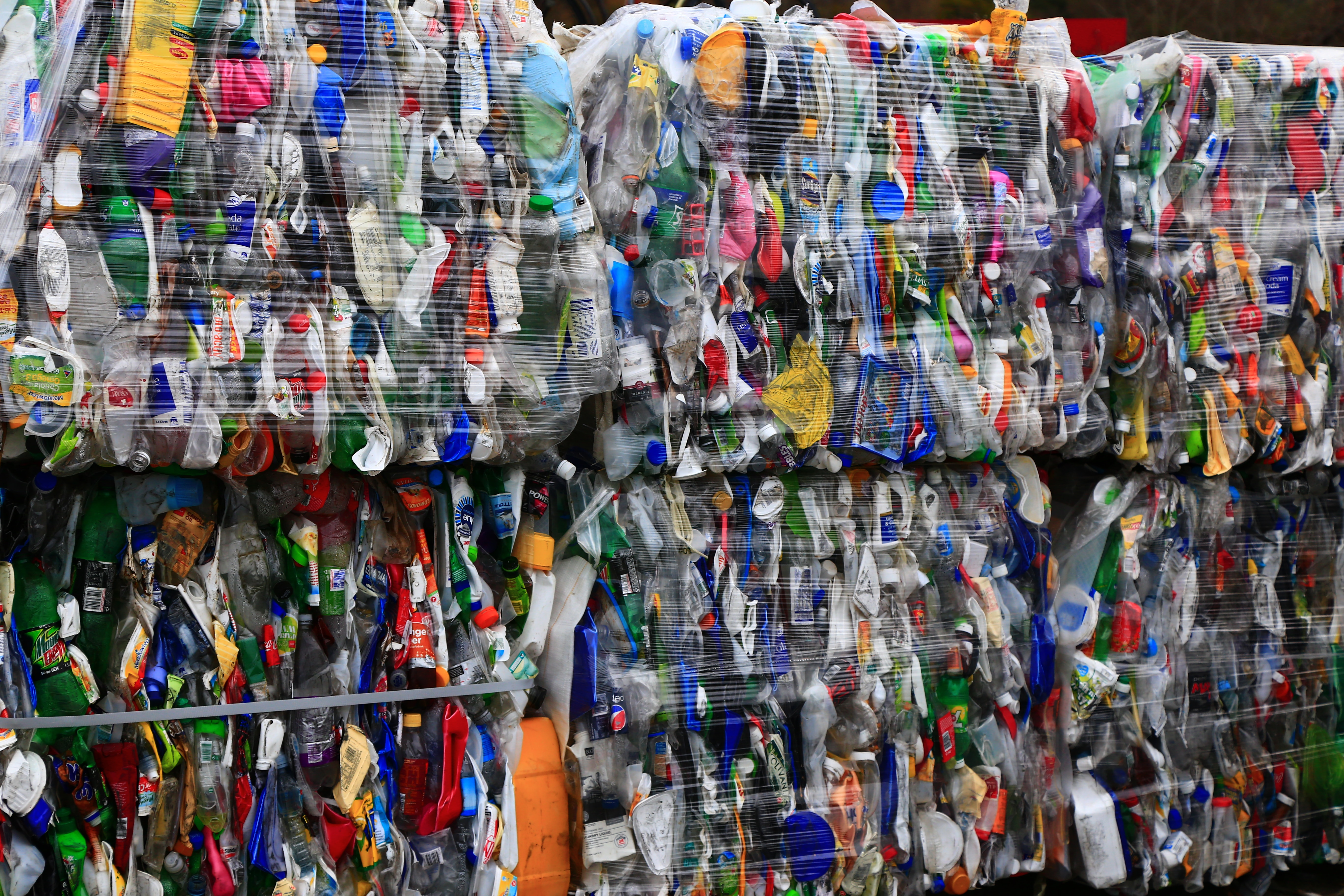Bales of used plastic containers tightly packed for their journey to be recycled.