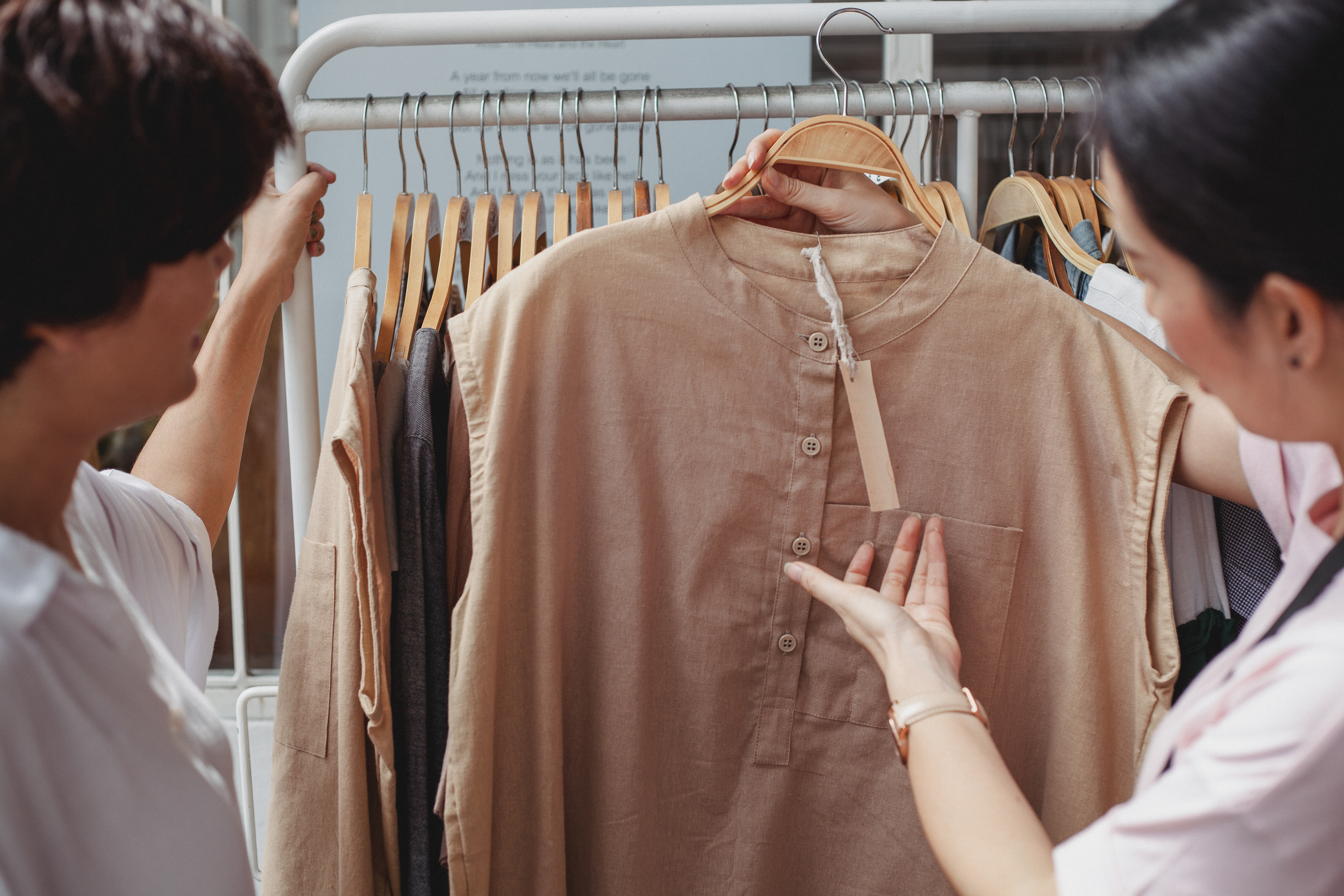 Crop asian shoppers interacting while choosing clothes in shop