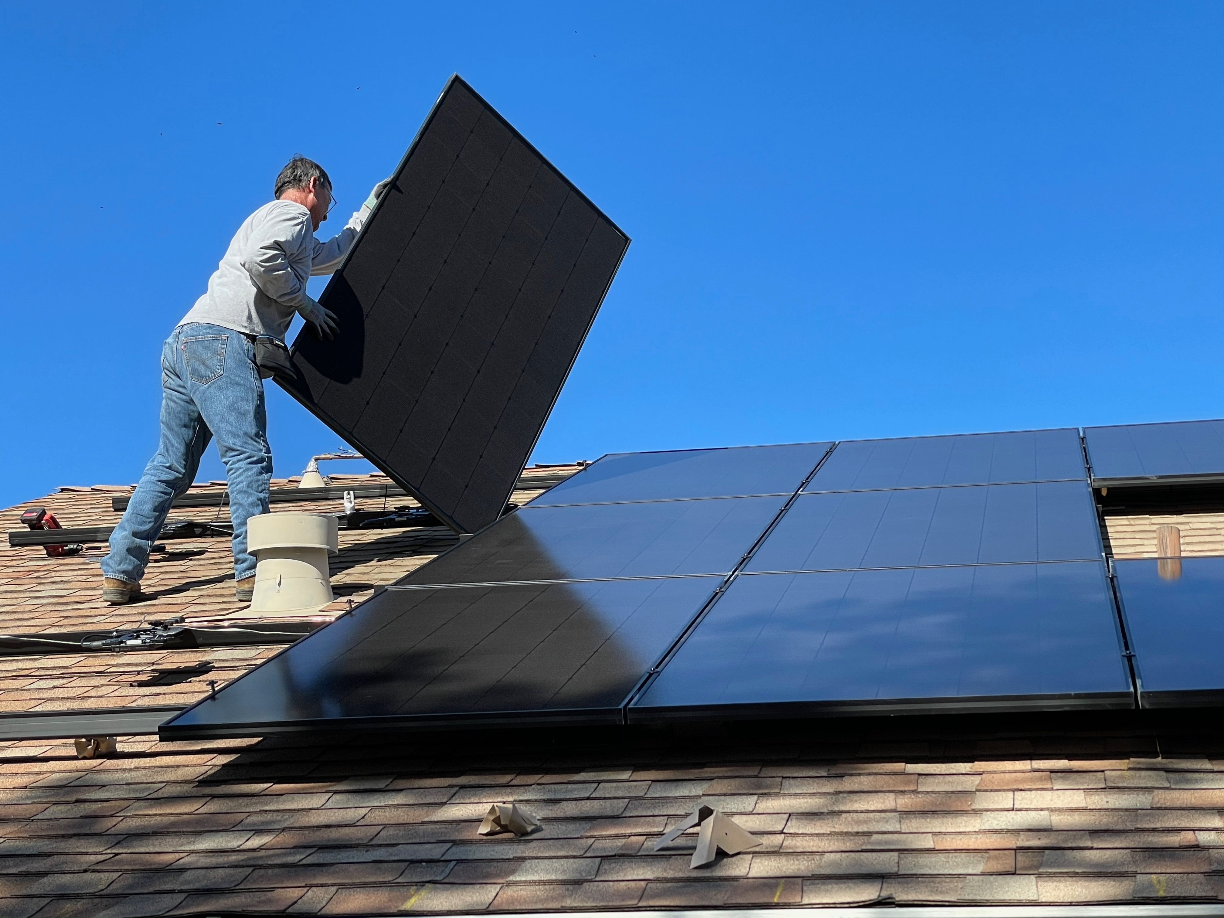 Worker installing solar panels on a roof